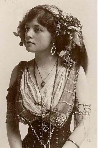 What a stunning young woman in her marvelous flavors of gypsy. I love the big hoopy bangle earrings and high cinched waist skirt, the vest and drapey blouse, the scarf, and the chains of her finery.