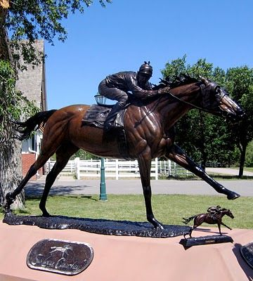 "Seabiscuit. The statue captures the moment when George Woolf called out to his opponent, ""So long, Charley!"" as Seabiscuit surged to the lead, and beat the War Admiral by four lengths."
