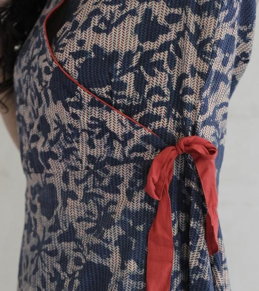 Or indigo wrap dress is tailored in 100% pure cotton fabric. It features an overall floral pattern that is block printed using natural dyes.