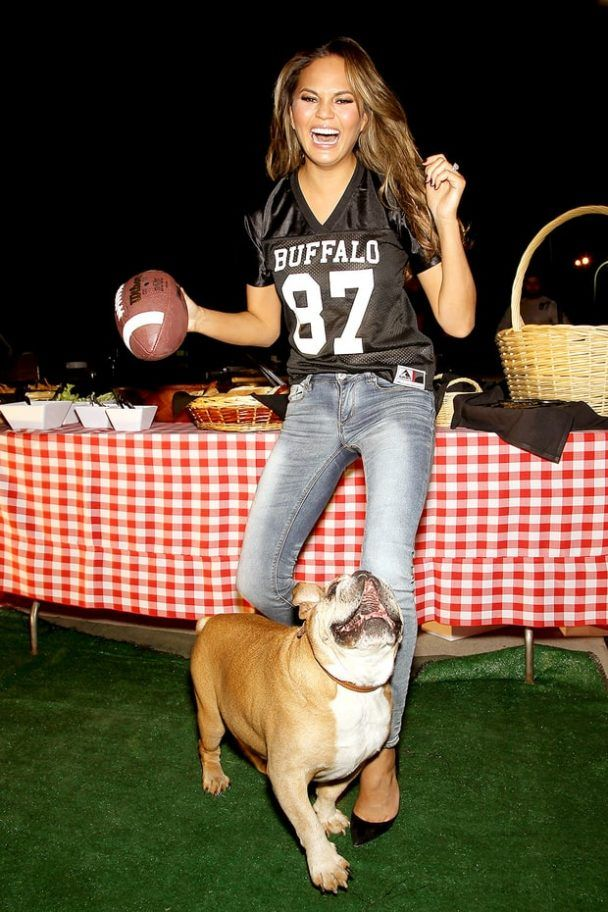Chrissy Teigen and bulldog, Puddy attends Jets vs. Patriots party. Looks like Puddy is having fun.