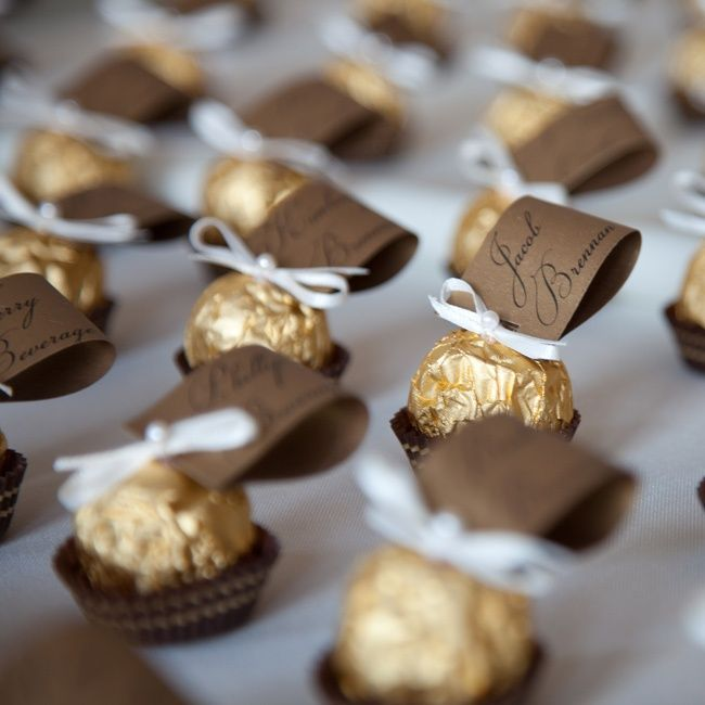 Ferrero Rocher chocolates were used to hold the escort cards. These edible treats were decorated with an ivory ribbon tie and topped with a ...