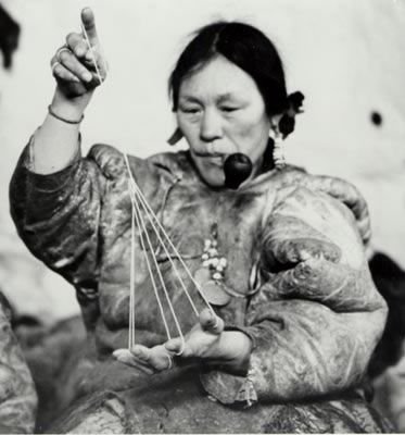 "Pikatnaaq's wife, Helen Konek's mother playing ""ajagaq"".  This game represents a tent. The person could include stories or little songs about the tent. These games were also important in building associations and personal relationships as well as passing along oral histories and traditions. String games were like picture shows and also developed important skills. As the person demonstrated the game, you had to guess what it would become. The games built memory, observation and creativity…"