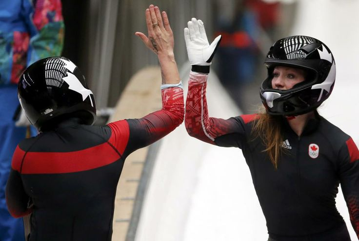 Canada's pilot Kaillie Humphries (L - Calgary, Alberta) high-fives teammate Heather Moyse (Summerside, Prince Edward Island) after they finished a run during the women's bobsleigh competition at the 2014 Sochi Winter Olympics February 18, 2014. REUTERS/Fabrizio Bensch (RUSSIA - Tags: OLYMPICS SPORT BOBSLEIGH)