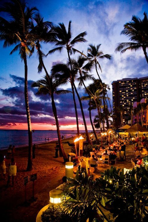 Honolulu, Hawaii. Walk along the beautiful beach boardwalk from one hotel to another. From one bar to another or just enjoy the romance of the lights and ocean.