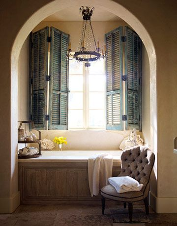 """Master Bath:     """"The blue shutters in the master bath are one of the few painted surfaces in this entire house,"""" Cummings says. """"But it's the original paint."""" BainUltra Tub. Chandelier from Watkins Culver Antiques."""