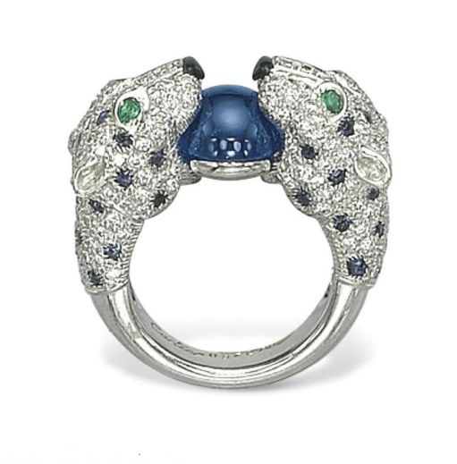 A DIAMOND, SAPPHIRE, EMERALD AND ONYX RING, BY CARTIER   Designed as two pavé-set diamond panther heads, each with cabochon sapphire spots, pear-shaped emerald eyes and onyx noses, holding a cabochon sapphire collet in their mouth, 1990s, ring size 5¾, with French assay mark for platinum  Signed Cartier, no. 637279