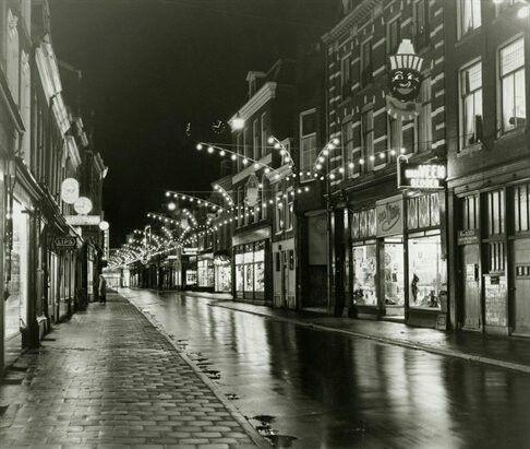 05/12/1956 beschrijvingGezicht in de Steenweg te Utrecht, bij avond, met feestverlichting ter gelegenheid van Sinterklaas.