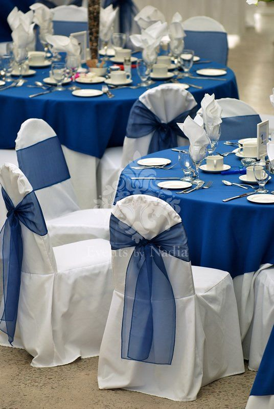 White Chair Covers With Blue Organza Sashes And Matching Blue Table Overlays
