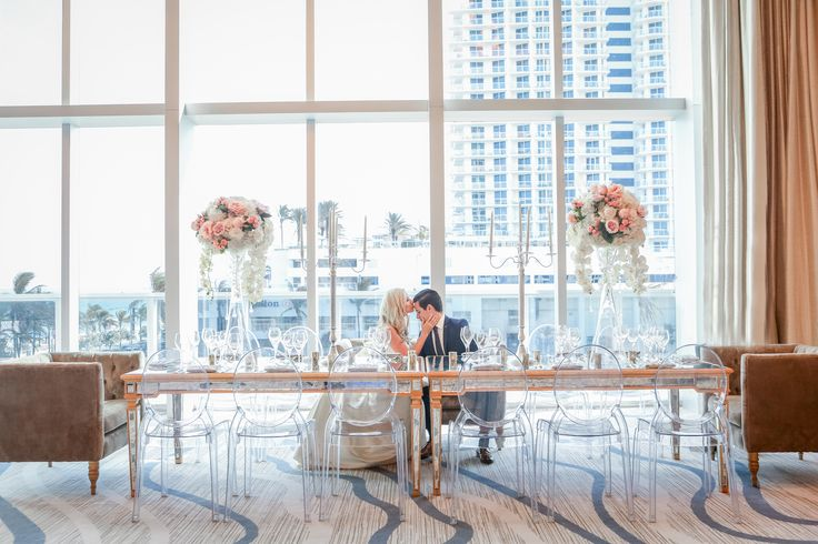 A kiss with a view at the Conrad Hotel in Fort Lauderdale Beach Florida. Those views to the beach are amazing and our head table for the bride and groom with candelabras and white and blush roses was perfect on mirrored tables. J Morgan Flowers, Emily Harris Photography