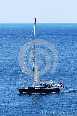 Black sailing boat with flag at the back is slowly traveling on the sea.