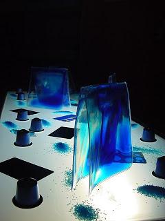 Gots de plàstic i cel·lofana de colors sobre la taula de llum.