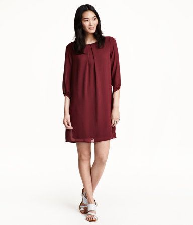 En rett skåret kjole i chiffon. Kjolen har en fold foran og trekvartlange ermer. Synlig glidelås i nakken. Trikotfôret.