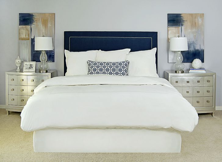 EJ Interiors - bedrooms - Abstract art, white bedding, navy blue upholstered headboard, nailheads, metallic Horchow nightstands, glass lamps, gray-purple walls, floral pillow, navy headboard, velvet headboard, blue velvet headboard, navy upholstered headboard,