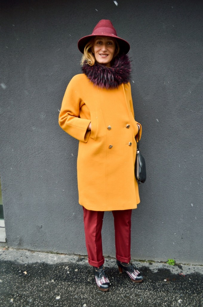 orange coat brightens up winter. Very cooly styled with that wide brimmed bordeaux hat and pants.