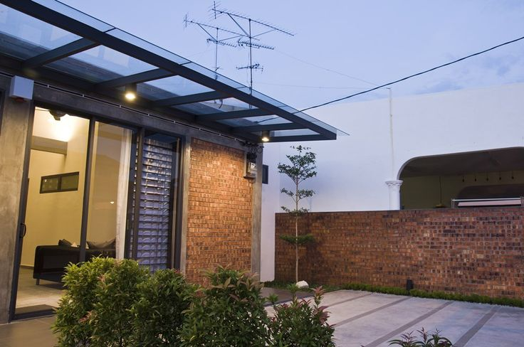 Raw industrial style single storey terrace house using exposed red bricks and rendered cement