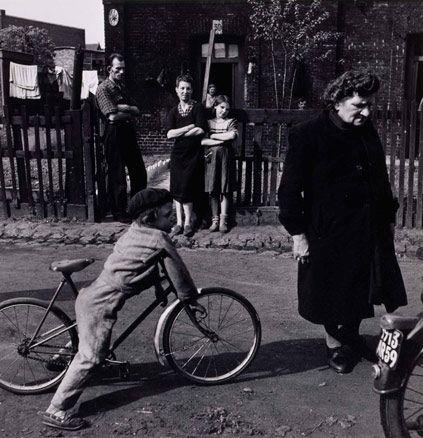 (J.-P. Charbonnier, Villejuif,1954) Ce cliché montre, au premier plan, un enfant sur une bicyclette et une vielle femme, et au second plan, une famille qui observe une scène que l'on ne voit pas. Cette image reflète le courant de la photographie humaniste car elle montre une scène de rue banale, familiale ou de voisinage, prise sur le vif, sans souci apparent de cadrage et d'esthétique. Elle met aussi en avant un objet essentiel du quotidien de l'époque: le vélo.