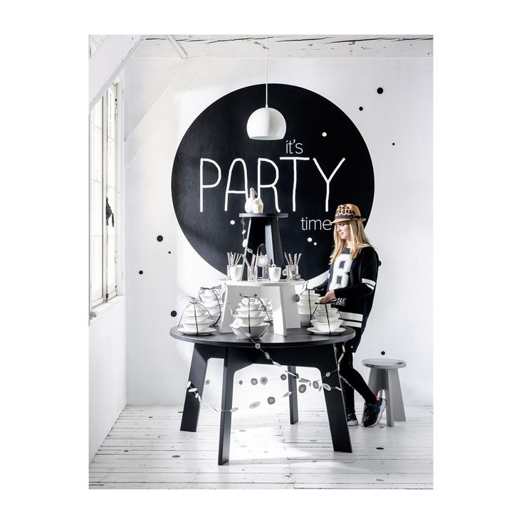 Black and white party table setting of white tableware, plates, and bowls, with a black bow, garlands and confetti on a black dining room table at a dinner party | Styling Kim Rossenberg | Photographer Sjoerd Eickmans | vtwonen may 2015 | #vtwonencollectie