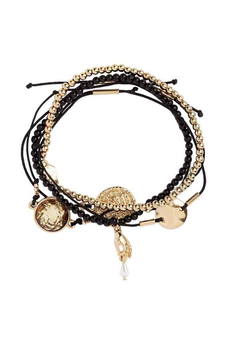 Lot de 5 bracelets: Bracelets avec breloques en plastique et métal. Deux modèles élastiques et trois en cordon. Longueur réglable.