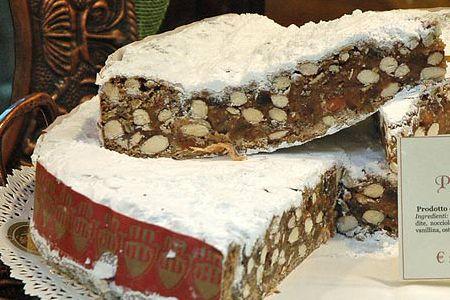 """PANFORTE DI SIENA IGP - La denominazione """"Panforte di Siena"""" identifica il prodotto dolciario ottenuto dalla lavorazione e successiva cottura in forno di un impasto a base di farina, frutta candita, frutta secca, miscela di zuccheri, miele e spezie. Il Panforte di Siena, che può presentarsi nella duplice versione bianca, se la copertura è a base di zucchero a velo, o nera, se la copertura è a base di spezie, si caratterizza al taglio per la presenza di mandorle intere ben distribuite e pezzi…"""