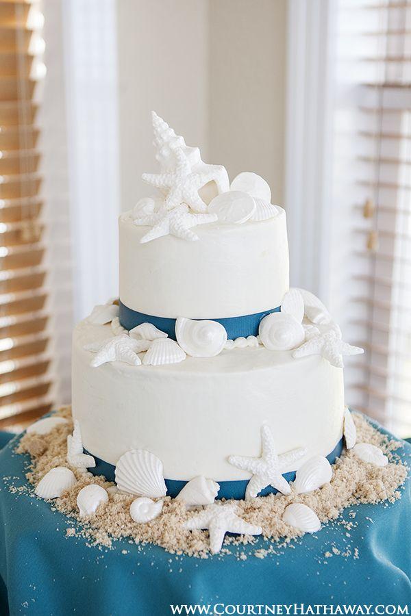 Bolo branco com detalhes em azul para casamento na praia.