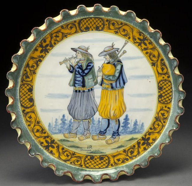 "Henriot Quimper pottery dish with pie crust edge centered by two Breton musicians, with an orange border painted with green decoration. Front signed ""HR Quimper"", back signed ""HR Quimper 1"" in blue under glaze. 12.25'' Dia., Circa - First quarter 20th C."