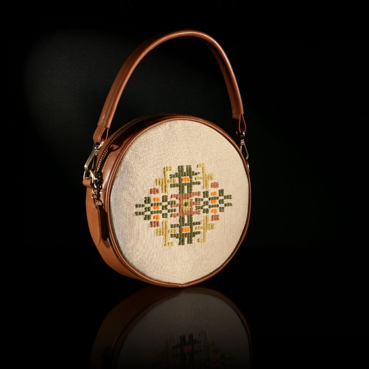 "The handmade woven round bag ""Iris"" adorns a pattern inspired of a traditional female outfit of Thrace. The color of the leather is tan and the background is in beige silk weaving"
