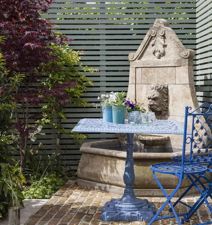 Salvaged stone fountain with yellow brick and contemporary slatted fencing. By Kingston Lafferty Design. www.kingstonlaffertydesign.com
