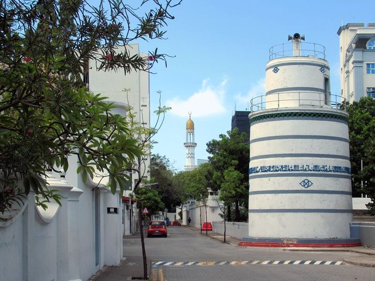 A round tower (1675) stands outside the Old Friday Mosque or Hukuru Miskiiy in Male, Maldives. The minaret of the Grand Friday Mosque is visible down the street.