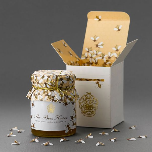The small white box resembles a bee have box with embossed ridges to denote planks of wood & nails. The famous Klein Constantia crest is gold foiled on the front of the box below the diecut slit that has one bee on its way into the box inviting you to open the packaging. The box opens to reveal a, bee covered, honey comb pattern as well as small diecut bees packaged inside each box. (Designer: Terence Kitching at At Pace design and Communication)