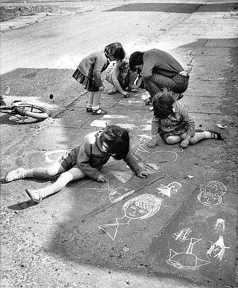 Street art: A group of children drawing on paving slabs with white chalk