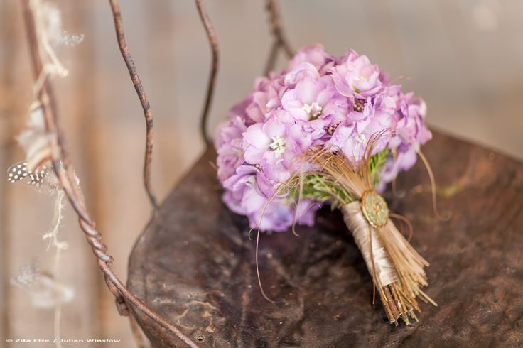 In an imagined forest clearing, a flower filled table is set for an intimate wedding breakfast. The branches above flutter with feather and twig garlands, tiny birds nestle and a pair of owls keep …