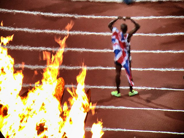 Mo Farah is seen through the heat of the Olympic flames after London 2012 10k win