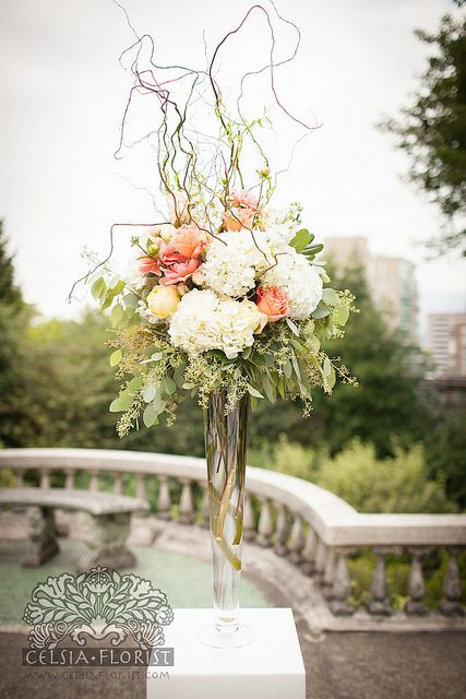 tall arrangement with hydrangea, roses, eucalyptus, and curly willow. Lush and updated classic aesthetic.