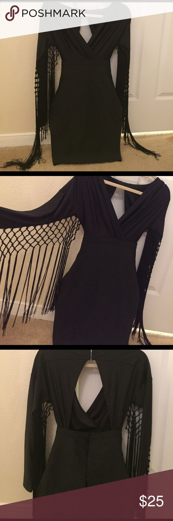 Sexy black dress✔️😍 Brand new never worn without tags! Bought from a Saks Sale! Super sexy black dress! Bandage material starting from the bust down fits tight! ✔️ has long sleeve with fringe hanging from them! ✨ Does have a small hole in the back wear the zipper is!!! See in the last picture! Was like that when purchased very easy to get fixed! ✨ WOW couture Dresses Mini