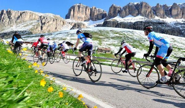 Alcuni ciclisti e, sullo sfondo, lo spettacolo naturale delle Dolomiti.