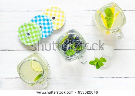 Summer lemonade in three colorful mason jars, top view. Fruits, mint and ice cubes in the background.