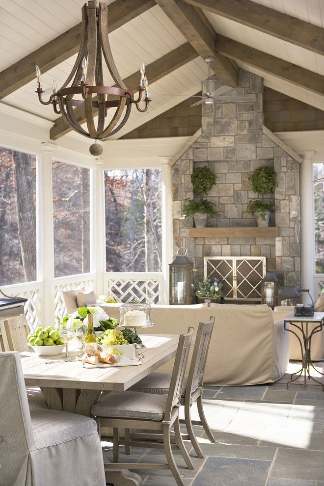 Large stone fireplace, vaulted ceiling with wood beams, wood dining table, rustic chandelier, stone patio | Linda McDougald Design