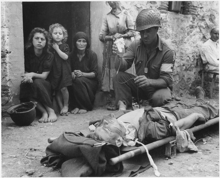 Private Roy W. Humphrey of Toledo Ohio is being given blood plasma after he was wounded by a shrapnel in Sicily on 9 August 1943 [3000x2421]