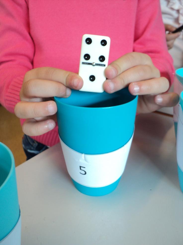 Dominorekenen: Via de dominostenen kunnen de leerlingen hun sommen of splitsoefeningen inoefenen op een actieve manier en met speels materiaal. De kinderen verwoorden dan bv: 4 + 1 = 5, deze steen mag in het potje van 5. Of 5 kan je splitsen in 4 en 1.