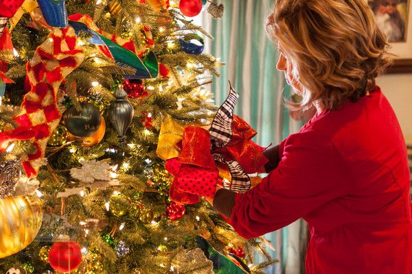 Kathy wires her bow on the Christmas tree