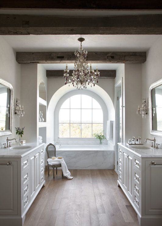 Stunning master bathroom centers on an arched alcove filled with arched window over a large soaking tub framed by a white marble surround flanked by built-in shelving to the left and a glass walk-in shower to the right below rustic wood beam ceilings adorned with a large crystal chandelier.