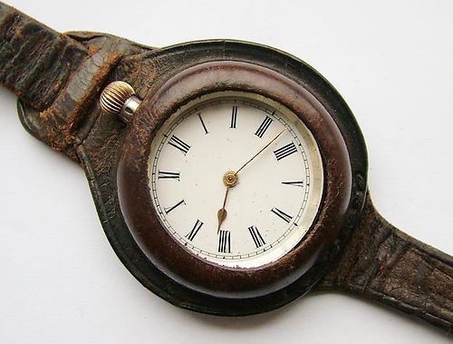 """The very first type of """"trench watch"""": WW1 era sterling silver gents trench watch conversion, with original leather band.   This is a pocket watch with a molded leather band that makes it a """"wristwatch.""""  The watch slips in through a slit at the top.  The watch is safer and the metal doesn't gleam, so if you don't want the Boches to shoot you, this is the way to go."""