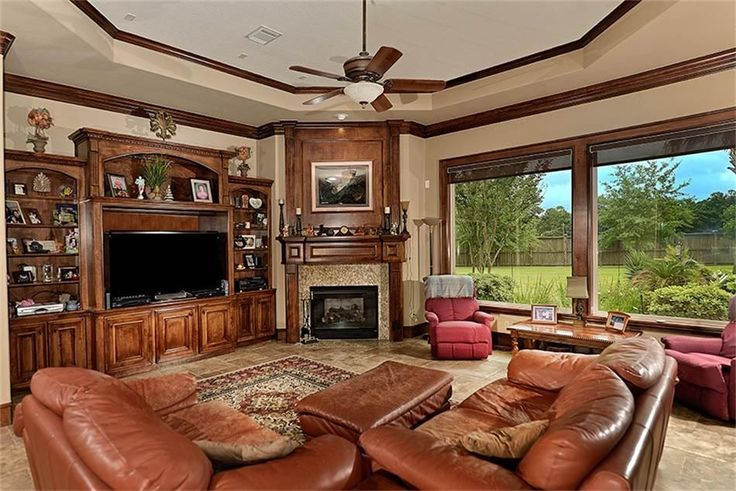 Traditional Living Room with Brown All Leather Loveseat, Built-in bookshelf, travertine tile floors, Crown molding