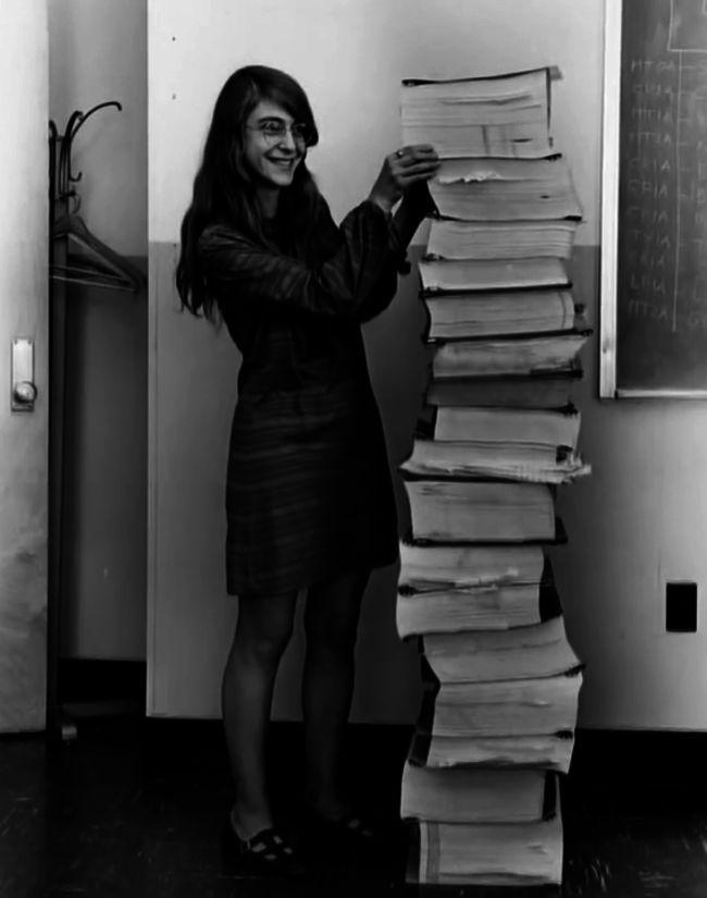 Margaret Hamilton, líder de engenharia de software do Projeto Apollo, ao lado do código  que ela escreveu à mão e que foi usado para levar a humanidade à lua – 1969