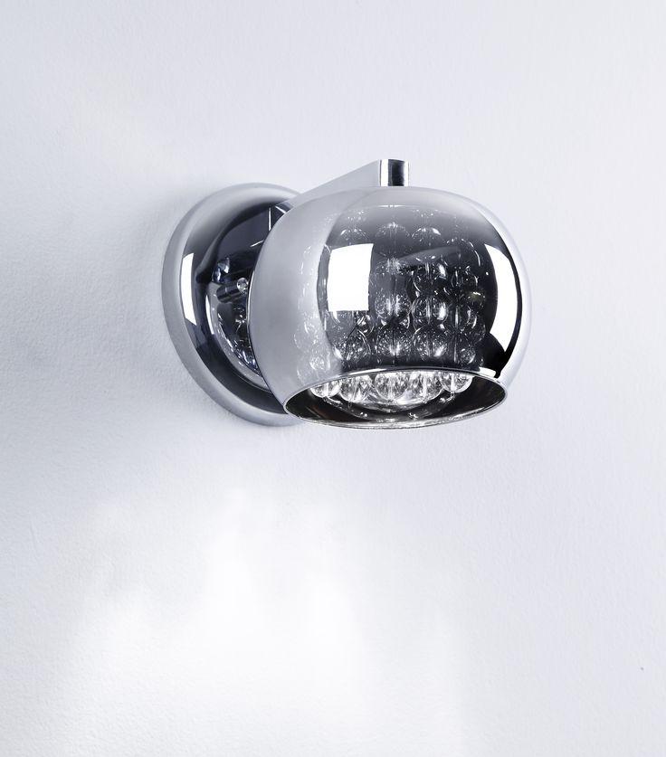 Ekskluzywny kinkiet z kolekcji Zuma Line Crystal wykonany z chromowanego metalowego korpusu i szklanego kloszu dodatkowo ozdobionego kryształkami, jest unikatowym i nowoczesnym rozwiązaniem oświetlenia salonu, jadalni, kuchni, czy też sypialni oraz przedpokoju, zarówno w eleganckim w stylu glamour jak i w minimalistycznym, skandynawskim klimacie.