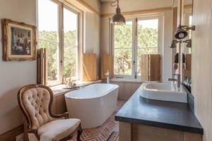 Übergangszeit Badezimmer, das weiße freistehende Badewanne und passende Waschbecken hat. / Foto von Wynand Wilsenach Architekten