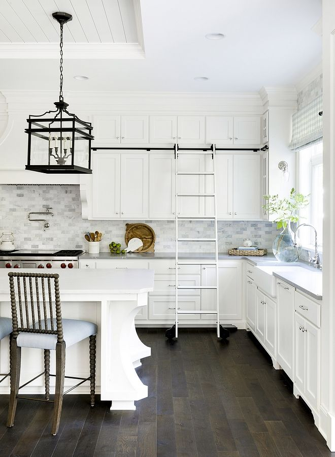 White kitchen with spool barstools, bobbin spindle and black lanterns New Construction Grey Shingle Home