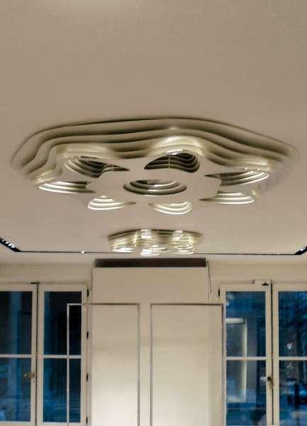 c.paris   Viabizzuno   luminaria para interiores IP20, realizada con placas superpuestas de aluminio pulido o barnizado en blanco, con orificios perfilados para alojar lámparas de halogenuros GX8,5 con alimentadores. disponible en las versiones de diámetro 1000mm (6 faros, uno central de 70W y 5 radiales de 35 W orientables) y diámetro 1700 mm (8 faros, uno central de 70W y 7 radiales de 35W orientables).