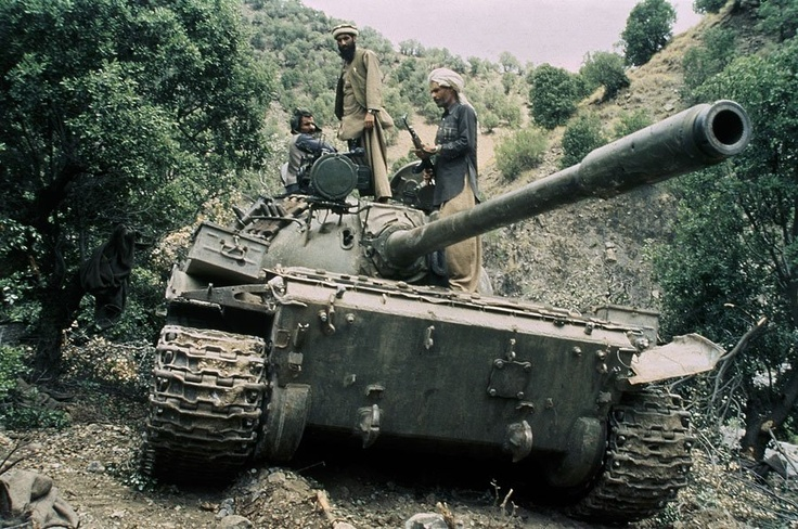 Mujahedeen guerrillas sit atop a captured Russian T-55 tank in 1988