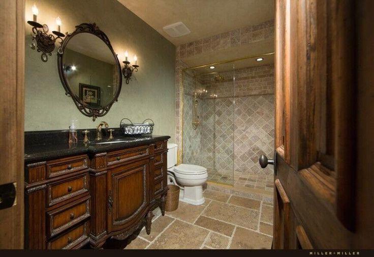 Dies ist ein traditionelles schauendes Badezimmer mit einer aufwendigen Hartholz Kabinett gekrönt mit einem dunklen Eitelkeit Zähler und unter montierten Waschbecken. Die abgerundeten Spieglein an der Wand fügt hinzu das altmodische aussehen, wie die vielfältigen geschnittenen Boden und Dusche Marmorwand.